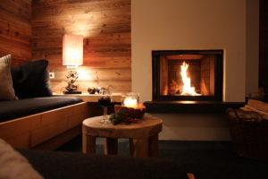 Das loderne Feuer im Kamin, das Glas Wein und die gemütliche Couch laden zum entspannen ein
