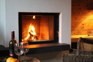 Das Feuer brennt im Kamin ein Glas Wein - das ist Genuß pur