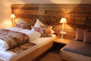 Die Stoffe im Schlafzimmer aus Altholz zeigen Hirsche und Jagdmotive und passen perfekt zum alpenländischen Interieur