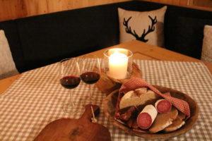 Das Appartement mit Kamin im Chalet Tannenhof mit offener Wohnküche und vom Tischler gezimmerte Einrichtung eine gute Tiroler Brotzeit