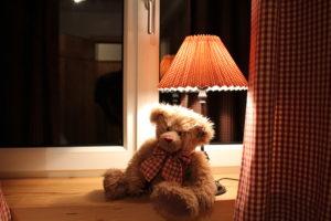Der knufflige TeddyBär sitzt unter der Lampe im Fenster