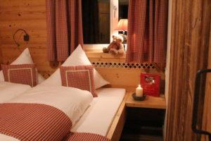 Das Schlafzimmer mit angrenzendem Badezimmer aus Altholz gezimmer mit rotkarierten Vorhängen und ganz besonders gemütlicher Atmosphäre