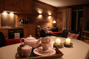 Das alte Holz des Appartements verbreitet Ruhe und Gemütlichkeit und der Duft ist unverwechselbar. Das Geschirr auf dem Tisch ist Gmundner Keramik handbemalt in Österreich